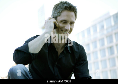 Man in black shirt talking on his mobile - Stock Photo