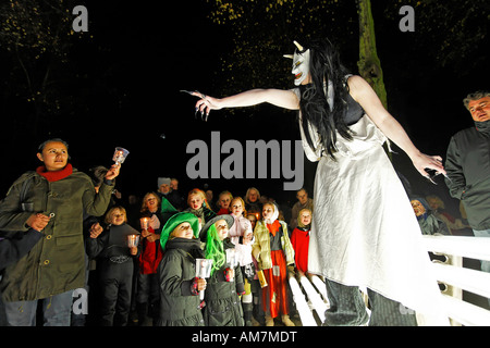 Young girl dressed up as a witch frightening a crowd of children, Halloween event, theatre museum Duesseldorf, NRW, - Stock Photo