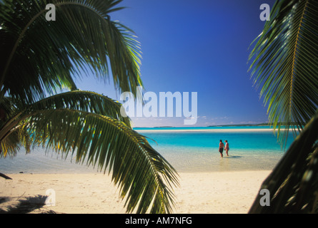 Tourist couple holding hands walking along beach on One Foot Island on Aitutaki in the Cook Islands - Stock Photo