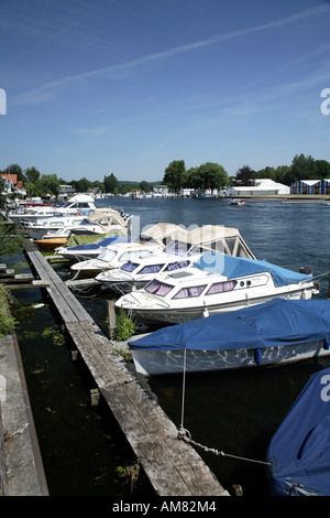 View of river Thames looking downstream towards royal regatta course and Phyllis Court with moored boats in foreground - Stock Photo