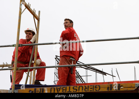 Two worker work at a construction site for a new office building in Hamburg, Germany - Stock Photo