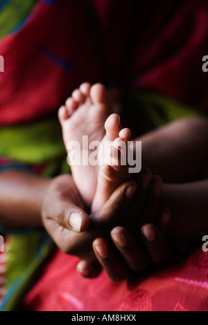 Indian mother holding babies bare feet. India - Stock Photo