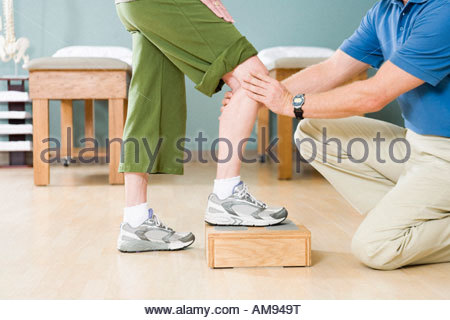 Physical therapist stretching woman's knee - Stock Photo