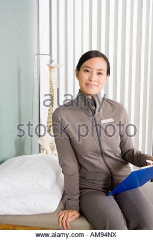Asian female physical therapist holding chart - Stock Photo