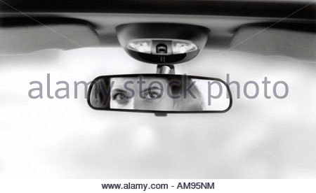 Woman's reflection in car rear view mirror - Stock Photo