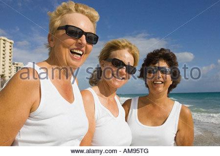 Three senior women wearing sunglasses at beach - Stock Photo