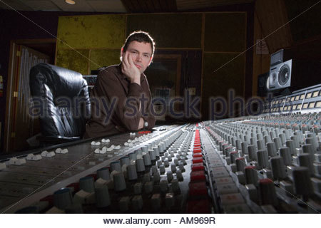 Producer in studio with sound equipment - Stock Photo