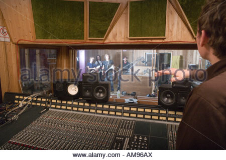 Producer signalling to band in recording studio - Stock Photo