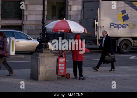 Newsprint. Street vendor selling the sun newspaper, with  paper van in background - Stock Photo