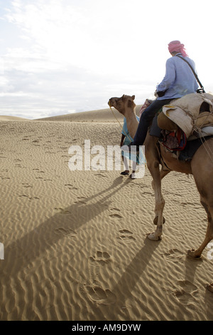 A tourist is led on a camel safari by an experienced guide through the Thar Desert in Rajasthan, India. - Stock Photo