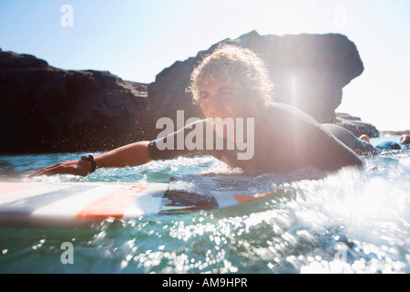 Man lying on surfboard in the water. - Stock Photo