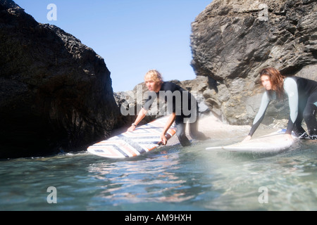 Couple in the water with surfboards. - Stock Photo