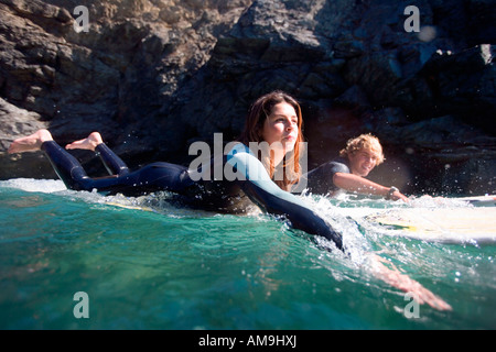 Couple lying on surfboards in the water smiling. - Stock Photo