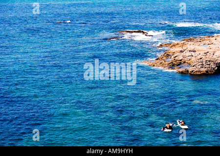 Couple lying on surfboards in the water. - Stock Photo