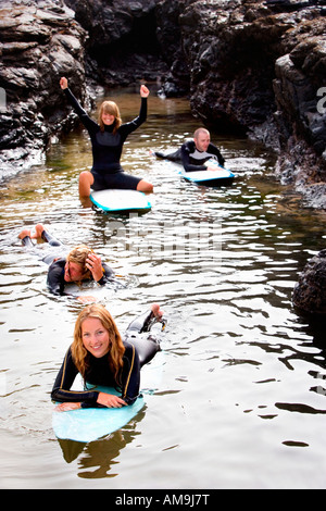 Four people having fun on surfboards in the water smiling . - Stock Photo