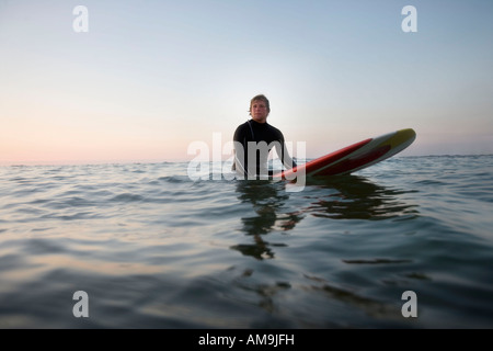 Man sitting on surfboard in the water. - Stock Photo