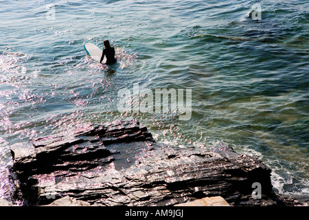 Woman sitting on surfboard in the water. - Stock Photo