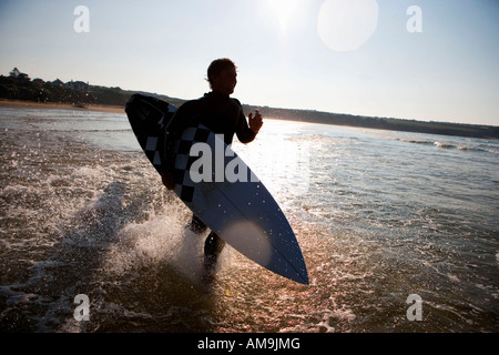 Man running through the water with surfboard smiling. - Stock Photo