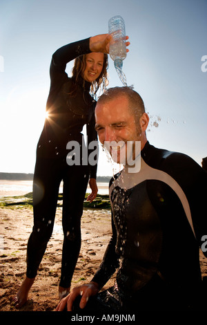 Woman pouring water over laughing man's head. - Stock Photo
