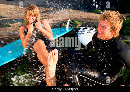 Couple splashing water on each other laughing with surfboards in background. - Stock Photo