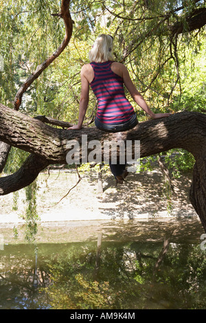 Woman sitting in a tree by a lake. - Stock Photo