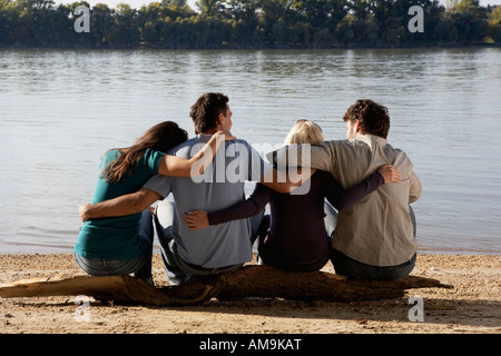 Four friends sitting on log by a lake with arms around each other. - Stock Photo