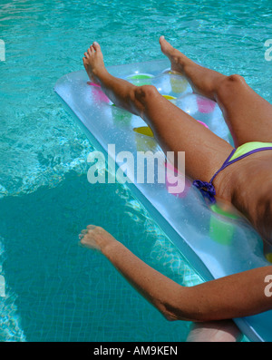 Woman floating in a pool. - Stock Photo
