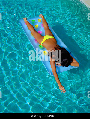 Woman floating in a pool on her stomach. - Stock Photo
