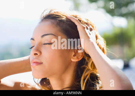 Woman outdoors with hands on head. - Stock Photo