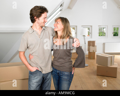 Couple moving into new home smiling. - Stock Photo