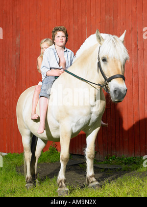 Young boy and young girl on a horse in front of a red wall. - Stock Photo
