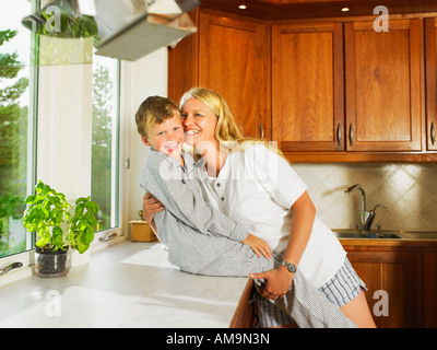 Woman and young boy embracing in kitchen smiling. - Stock Photo