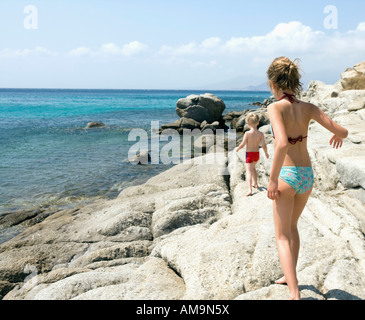 Young girl and young boy walking on rocks by the water. - Stock Photo