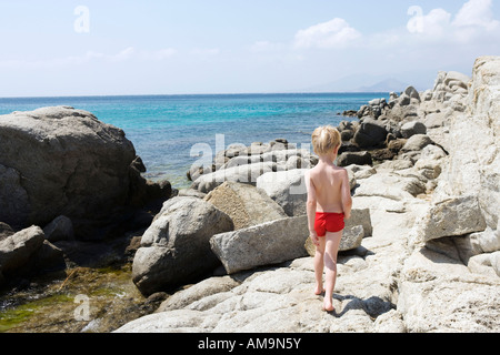 Young boy walking on rocks near the water. - Stock Photo