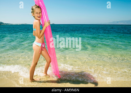 Young girl holding up an inflatable raft at the beach smiling. - Stock Photo