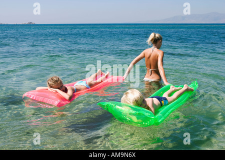 Woman pulling young boy and young girl on inflatable rafts. - Stock Photo