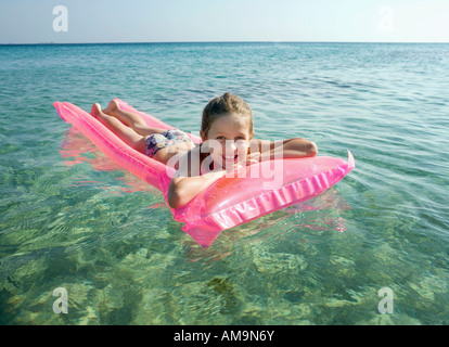 Young girl on an inflatable raft in the water smiling. - Stock Photo