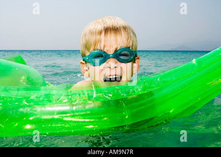 Young boy with an inflatable raft in the water with mouth open. - Stock Photo