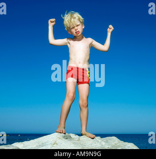 Young boy on large rock by the water flexing and scowling. - Stock Photo