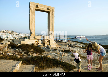 Woman with young boy and young girl pointing at the Portara in Greece with tourists in background. - Stock Photo