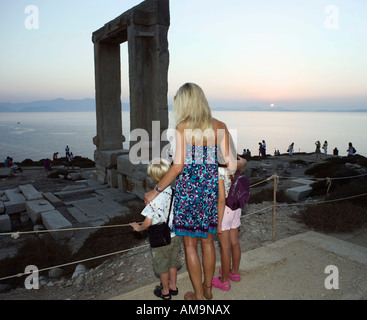 Woman with young boy and young girl looking at The Portara in Greece with tourists in background. - Stock Photo