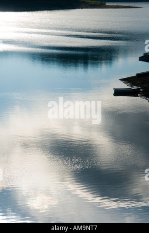 Smooth lake water surface and lonely boat, Lokve in Gorski Kotar in Croatia, Europe - Stock Photo
