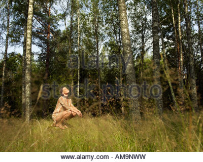 Woman crouching on a large rock in forest smiling. - Stock Photo