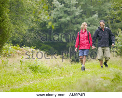 Couple walking hand in hand in a park smiling. - Stock Photo
