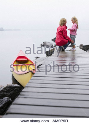 Woman with young girl standing on a dock smiling. - Stock Photo