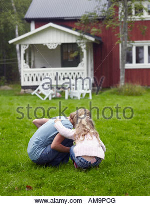 Woman with young girl crouched down in yard. - Stock Photo