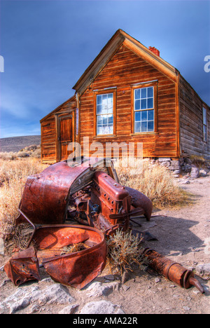 An abandoned, decaying vehicle sits outside of a derelict house in the ghost town of Bodie California Bodie was - Stock Photo