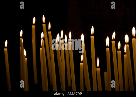 images of candles in churches in which a prayer is made and a candle lit to think about loved ones and others at - Stock Photo