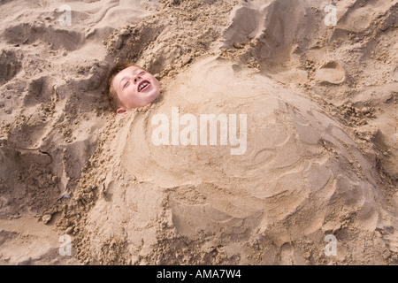 UK Dorset Swanage beach child buried up to neck in the sand - Stock Photo