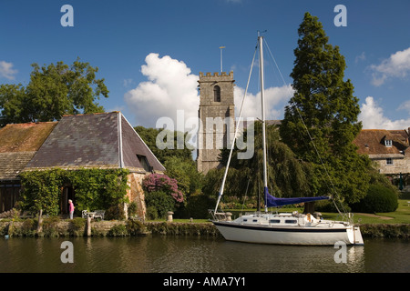 UK Dorset Wareham rowing boats on River Frome below St Marys Church and old Priory Hotel - Stock Photo